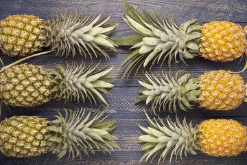 Row of pineapple fruits on blue wooden table background.