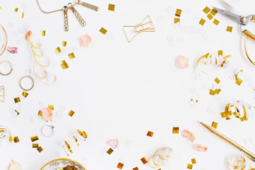 Beauty blog background. Gold style feminine accessories frame. Golden tinsel, scissors, pen, rings, necklace, bracelet on white background. Flat lay, top view.