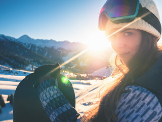 Portrait of snowboarder girl on the background of high mountain