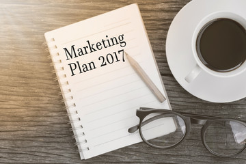 Concept  Marketing Plan 2017 message on notebook with glasses, pencil and coffee cup on wooden table.