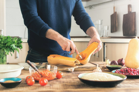Man cooking a butternut squash  on a wooden table