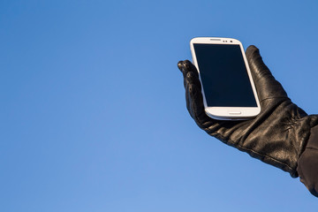 Hand in the glove holding a mobile phone on the blue sky background.