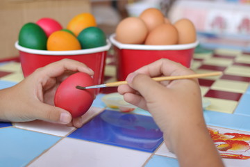 Selective focus and shallow depth of field. Easter eggs are painted with paintbrush by little boy.