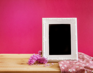 White vintage photo frame with sweet statice flower with on red pink background