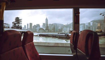 The skyscrapers of Hong Kong in background while ferry boat sail.