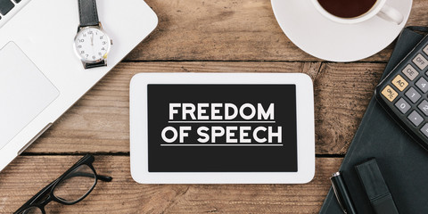 freedom of speech on phone on Office desk with computer technology, high angle