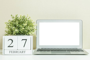 White wooden calendar with black 27 february word with white blank space at center of computer notebook on white wood desk and cream wallpaper textured background in selective focus at the calendar