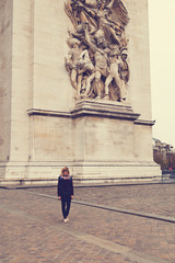 Girl posing in front of the Arc de Triomphe, Paris, France.