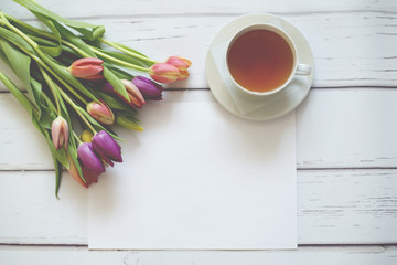 Bunch of colourful tulips on white background with a cup of tea and white sheet of paper