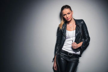 sexy blonde woman in leather clothes posing