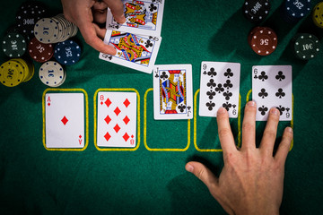 Poker concept with cards on green table. Hand-ranking categories: Flush