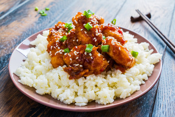 Crispy sesame chicken, chopped breast fillets, with a sticky sweet Asian sauce and white boiled rice on a plate on wooden table.