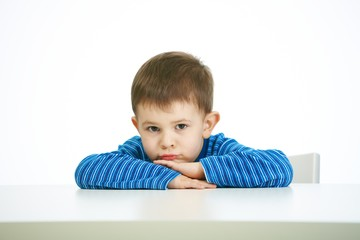 Portrait of sullen little boy sitting at table