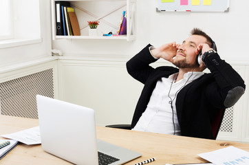 Young relaxed businessman listen music in modern white office