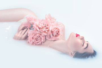 Beautiful fashion model girl with bright makeup and pink roses taking milk bath, spa and skin care concept