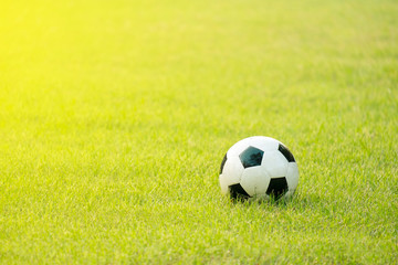 used soccer ball on a green field in the morning light. with warm tone color filter added.