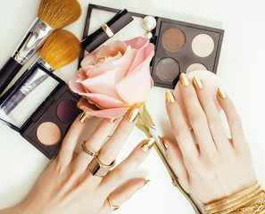 woman hands with golden manicure and many rings holding brushes, makeup artist stuff stylish, pure close up pink flower rose among cosmetic for makeup set