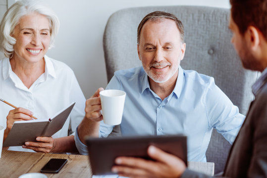 Smiling aged couple meeting with sales manager