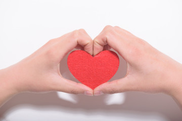 Valentines day and love concept.Two hands holding a red heart shape decoration on white background.