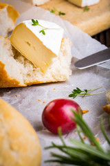 Cheese with white mold, radish, grapes and baguette with herbs