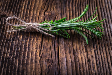 Fresh fragrant rosemary branch on vintage wooden table