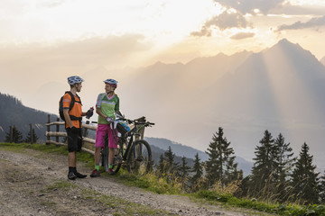Young couple of mountain bikers standing on dirt road during sunset, Zillertal, Tyrol, Austria
