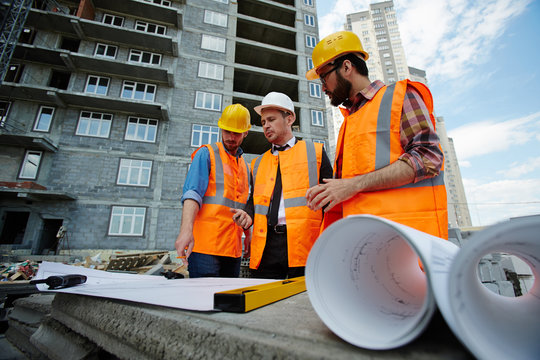 Low angle portrait of two workmen showing apartment building blueprints to inspector on construction site, all wearing reflective orange vests and hard hats