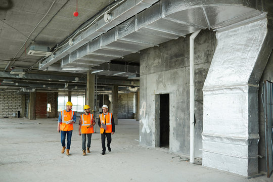 Group of three workmen wearing protective helmets and vests on construction site: walking among concrete walls at basement floor of unfinished building with foreman inspector, wide shot