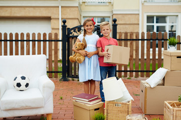Portrait of neat happy children, boy and girl, standing holding cardboard boxes, toys and surrounded by personal belongings outside, in front of their new house, smiling brightly, ready to move in