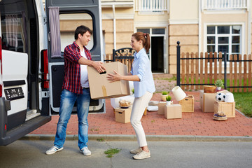 Portrait of man taking cardboard boxes out of moving van and passing them to his wife in front of new house