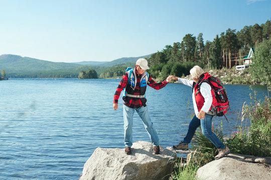Senior man helping his wife while hiking