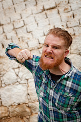 Portrait of angry red haired hipster man with blue plaid shirt
