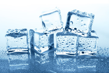 Transparent ice cubes group with reflection on blue glass with water drops