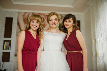Smilling bride with bridesmaids on red dresses indoor room.
