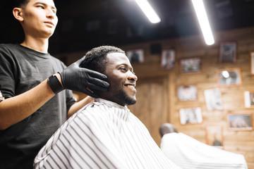 Happy man looking in mirror in barbershop