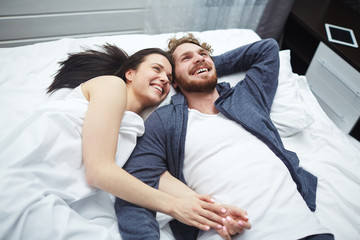 Joyful young couple relaxing in bed