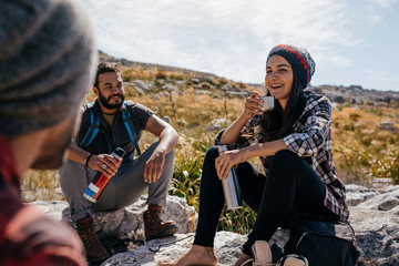 Young hikers relaxing and having coffee