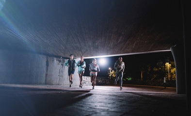 Young men and women jogging together at night