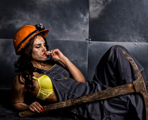 sexy female miner worker with pickaxe, in coveralls over his naked body, sitting on the floor on backdrop of steel wall and smoking