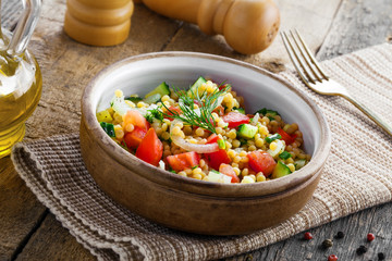 Salad made of couscous with vegetables in a bowl for healthy meal. Traditional Israeli Ptitim for lunch. Moroccan food.