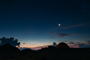 Tent on landscape against blue sky at dawn