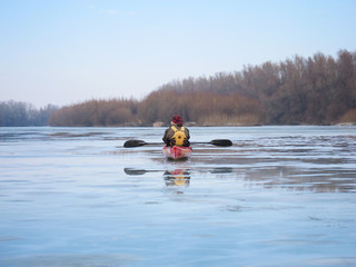 Man in red kayak on river is covered with ice. Winter kayaking on the river Danube. Winter kayaking on Danube river.
