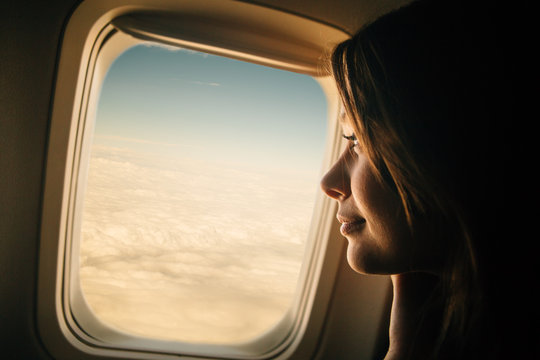 Young woman looking through window in airplane