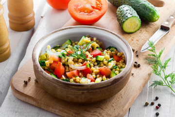 Healthy salad for breakfast made of couscous, tomatoes, cucumber and onion on a table. Cooking of traditional Israeli Ptitim meal and ingredients on a white wooden table. Moroccan cuisine food.