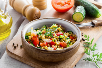 Traditional Israeli healthy meal Ptitim with tomatoes, cucumber and onion for delicious healthy breakfast. Cooking of classic Moroccan couscous with vegetables.