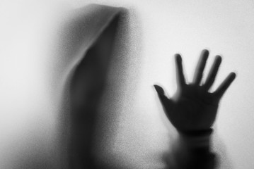 Shadow blur of horror man in jacket with hood.One hands on the glass.Dangerous man behind the frosted glass.Mystery man.Halloween background.Black and white picture.Blur picture.