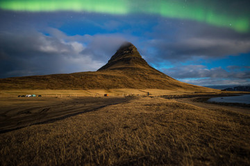 Aurora or the Northern light over the Kirkjufell mountain the iconic famous mountain in triangle shape in the west region of Iceland.