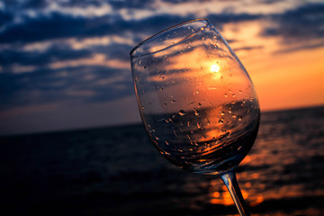 Wine glass on the beach at sunset with sun inside