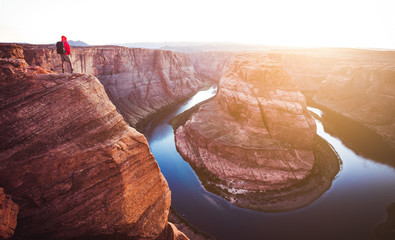 Wall Mural - Hiker overlooking Horseshoe Bend at sunset, Arizona, USA