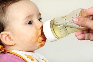 Ein Kleinkind trinkt Wasser aus einer Nuckelflasche